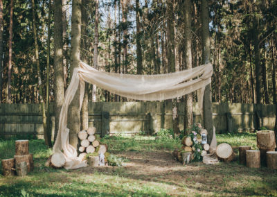 arch for the wedding ceremony of burlap and wooden logs in pine forest