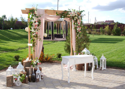 Arch for the Wedding ceremony, decorated with cloth flowers and greenery, is in a pine forest