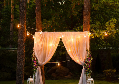 Wedding twilight ceremony decoration made of hanging on a tree golden lanterns and lamps and standing on the grass fired candles with the carpet in the middle
